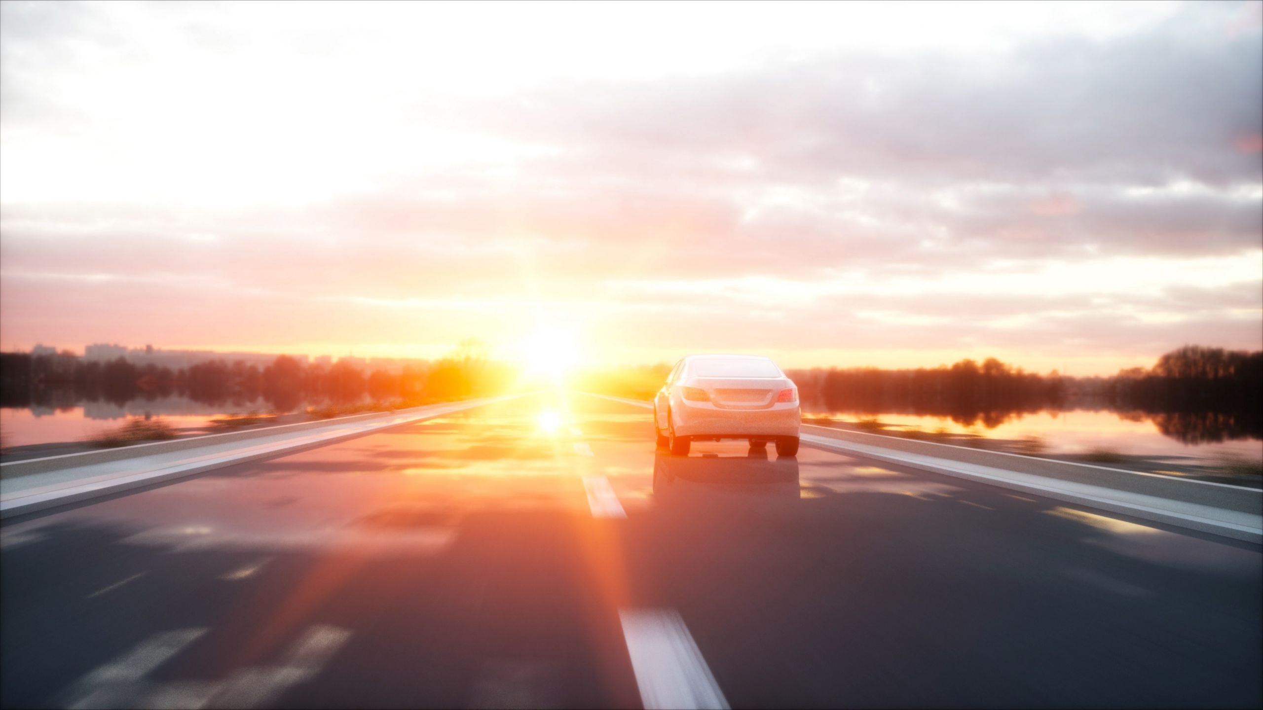 Car driving on the road into the sunset