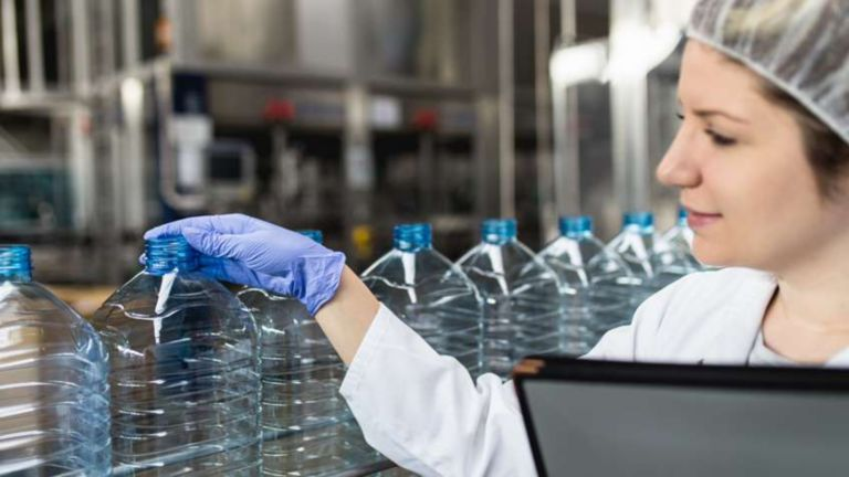 Young happy female worker in bottling factory checking water bottles before shipment. Inspection quality control.