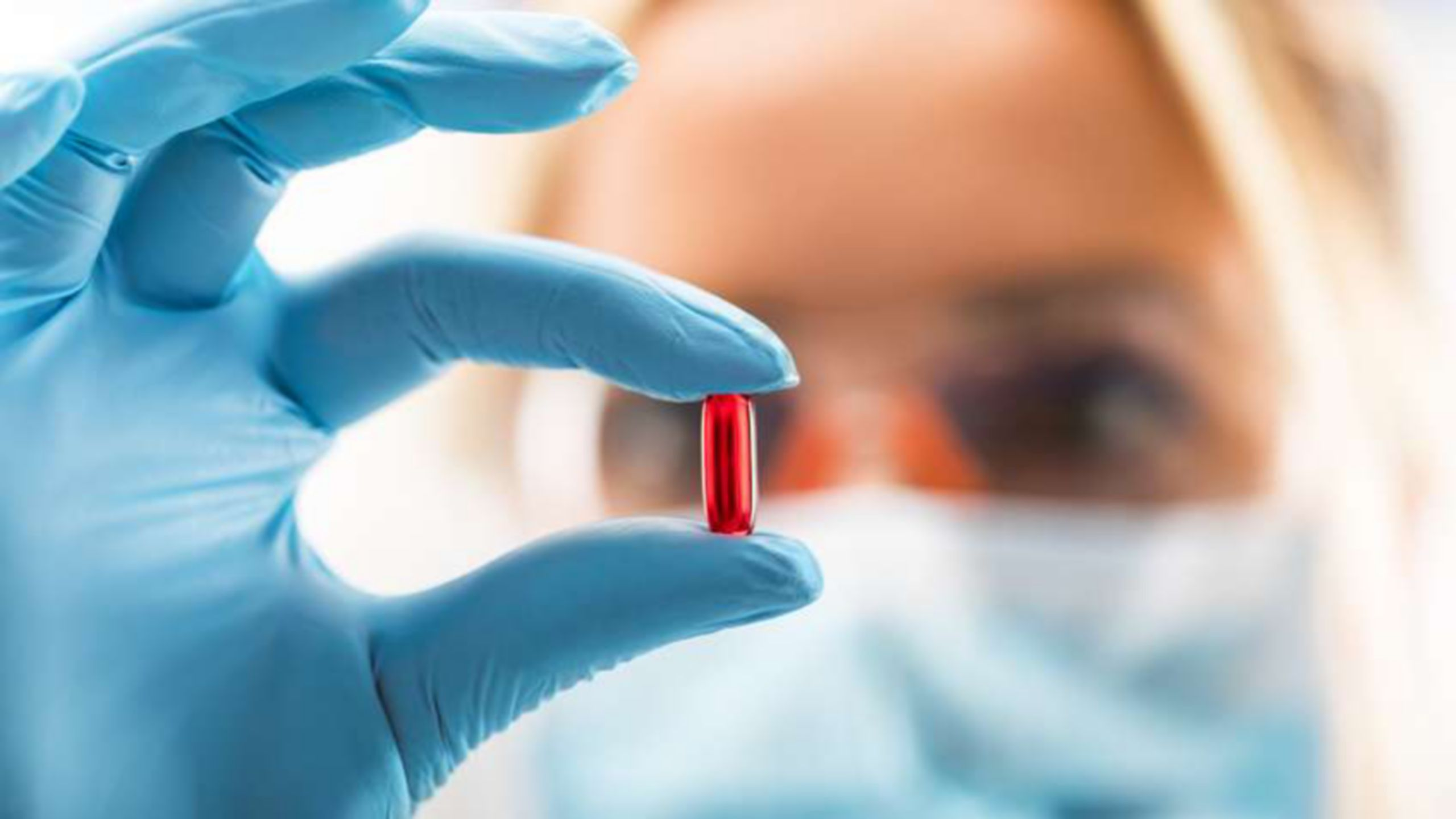 Young attractive female scientist with protective eyeglasses and mask holding a red transparent pill with fingers in gloves in the pharmaceutical research laboratory