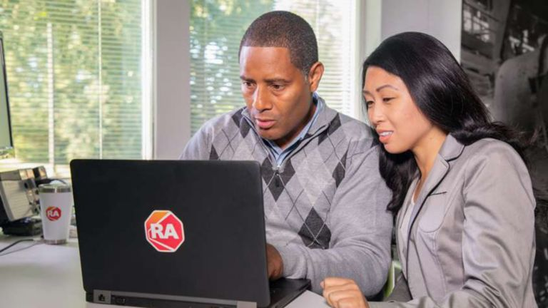 A male and a female employee sitting at a desk viewing information on a laptop with a Rockwell Automation logo