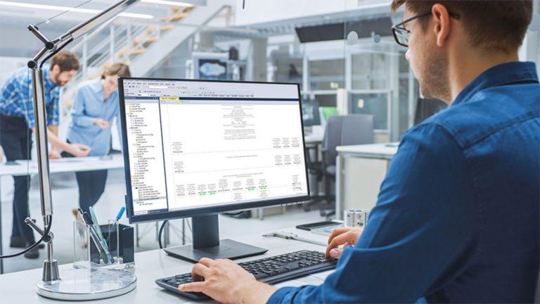Un empleado con lentes viendo software en el monitor de su escritorio con dos empleados en segundo plano colaborando en otro proyecto