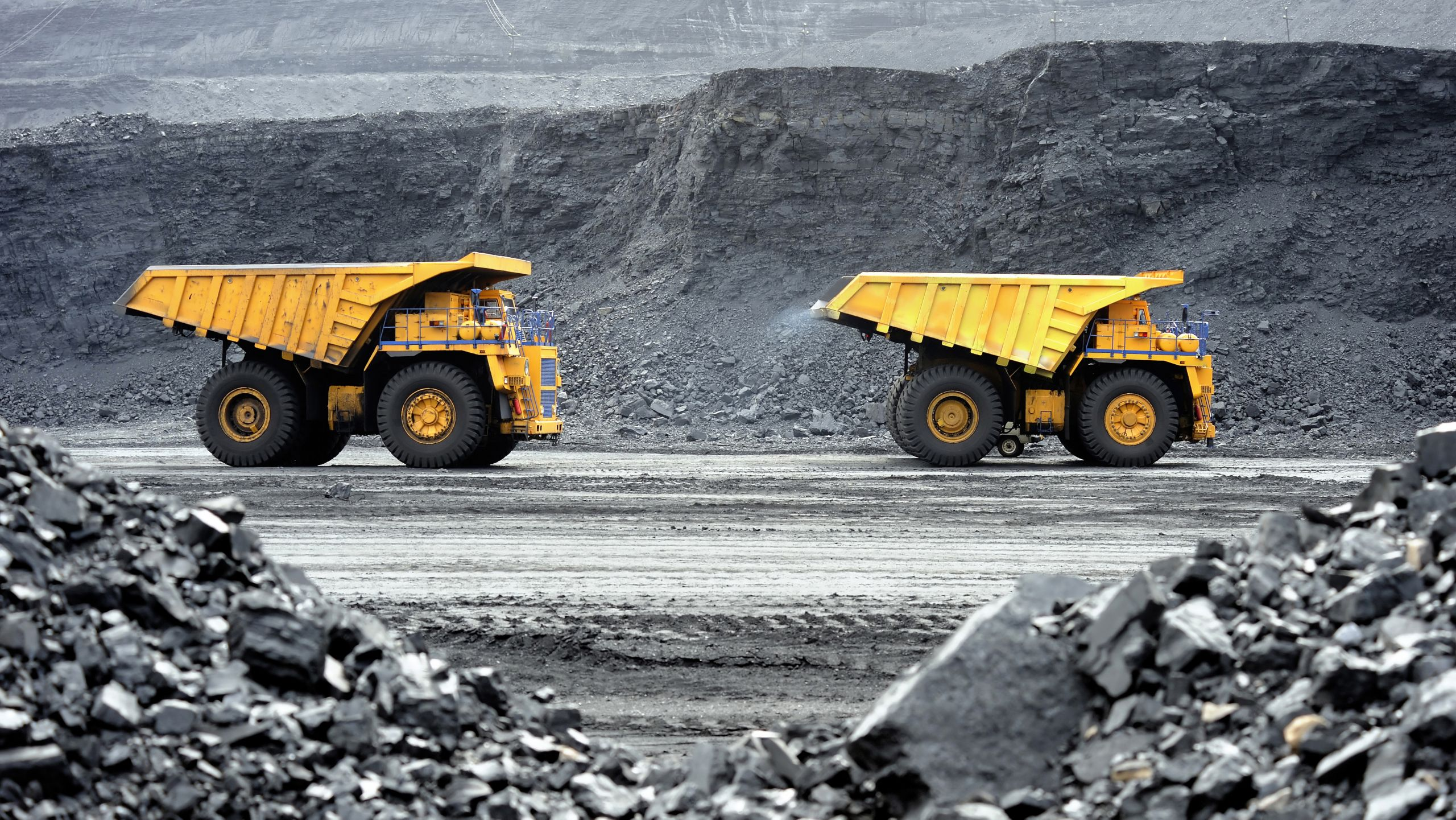 Two dump trucks driving at a mining site