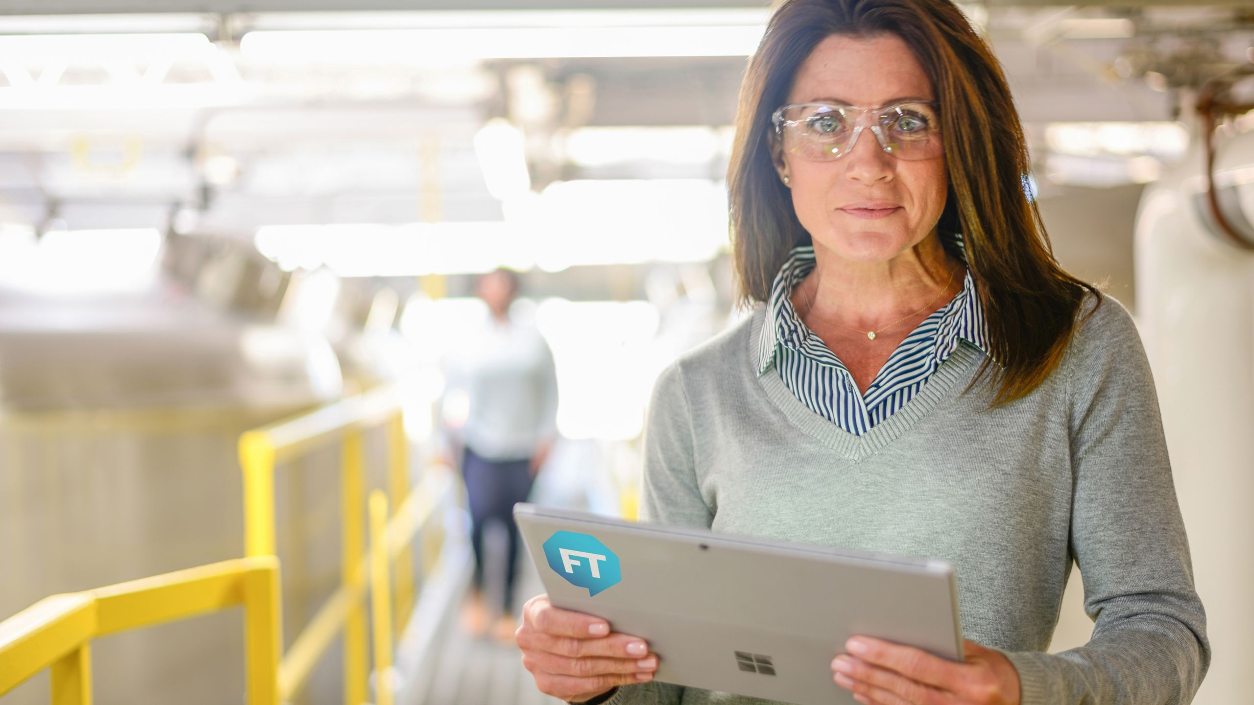 woman wearing safety goggles holding tablet with FactoryTalk sticker on the back inside of a manufacturing plant