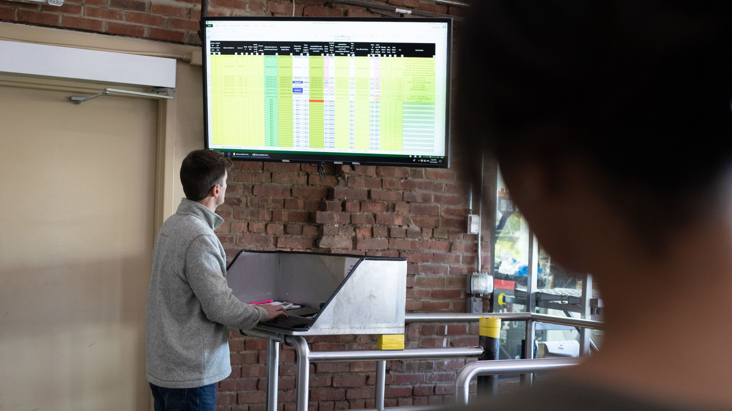 Rockwell Automation employee viewing FactoryTalk AssetCentre software on large monitor with coworker
