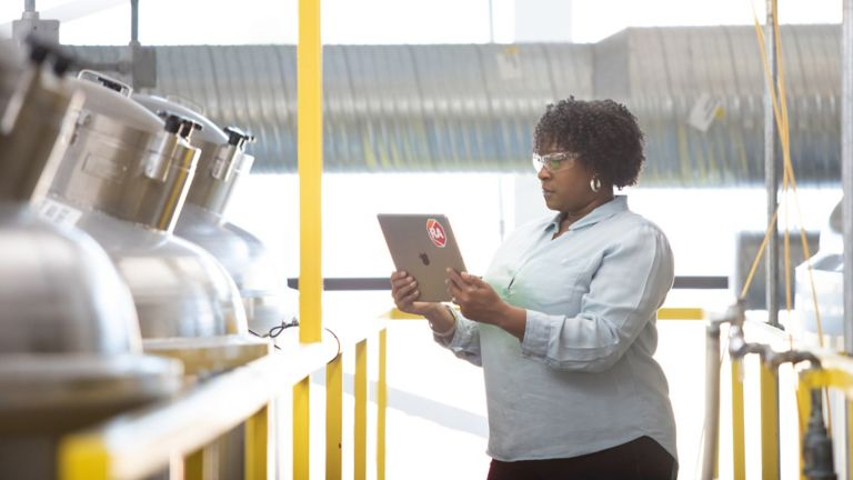 Female employee in a manufacturing plant holding a tablet with a Rockwell Automation logo assessing data from the FactoryTalk Batch software application