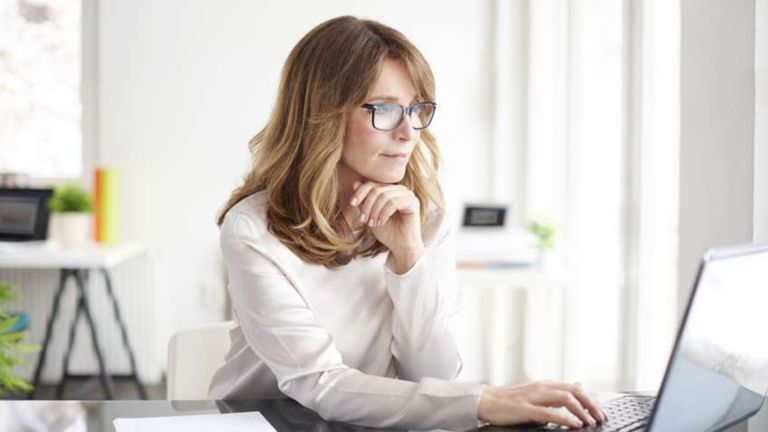 Female employee sitting in a casual office environment navigating through information on her laptop
