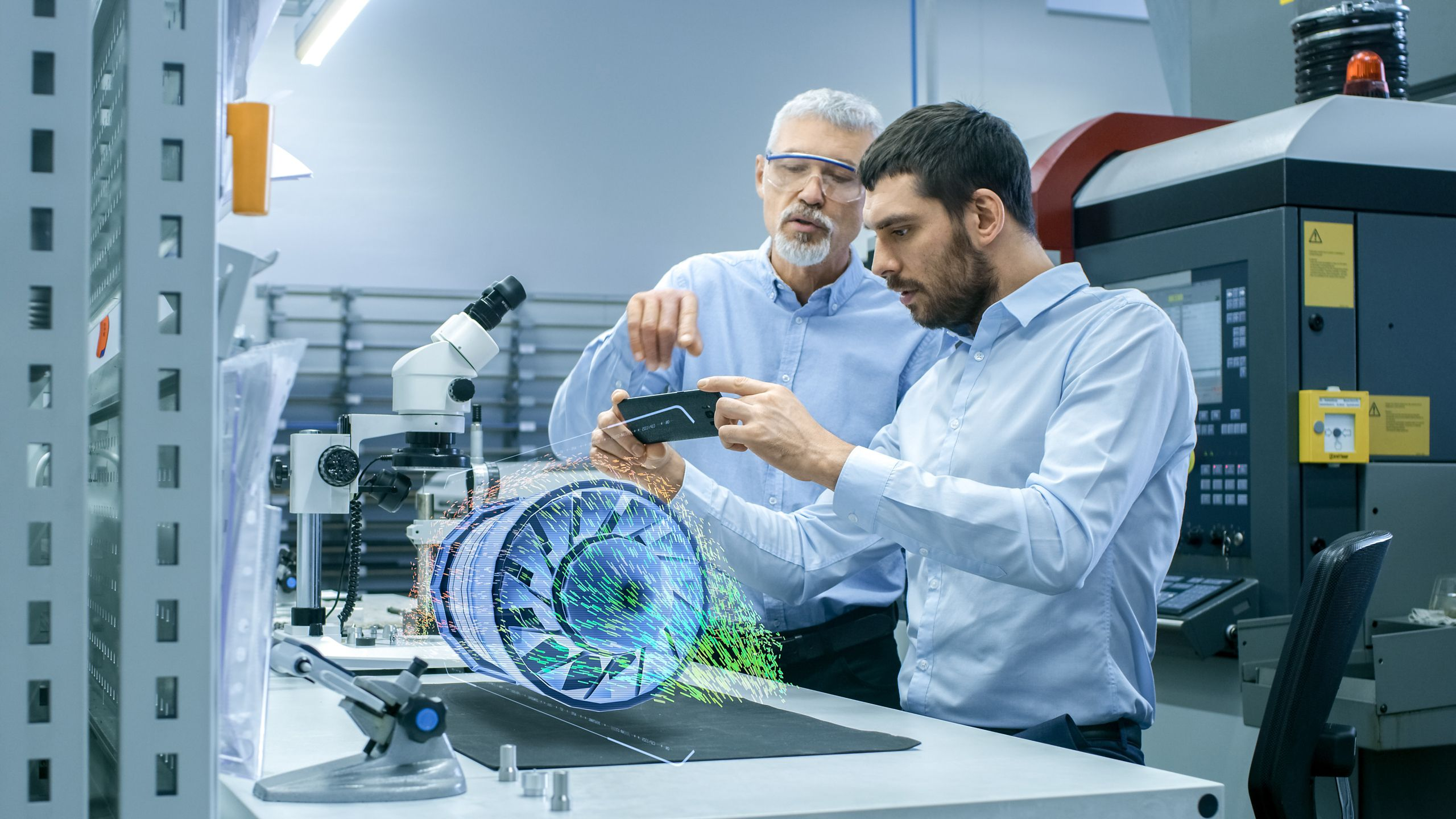 Two male engineers in a plant viewing a mobile phone with a part on a table