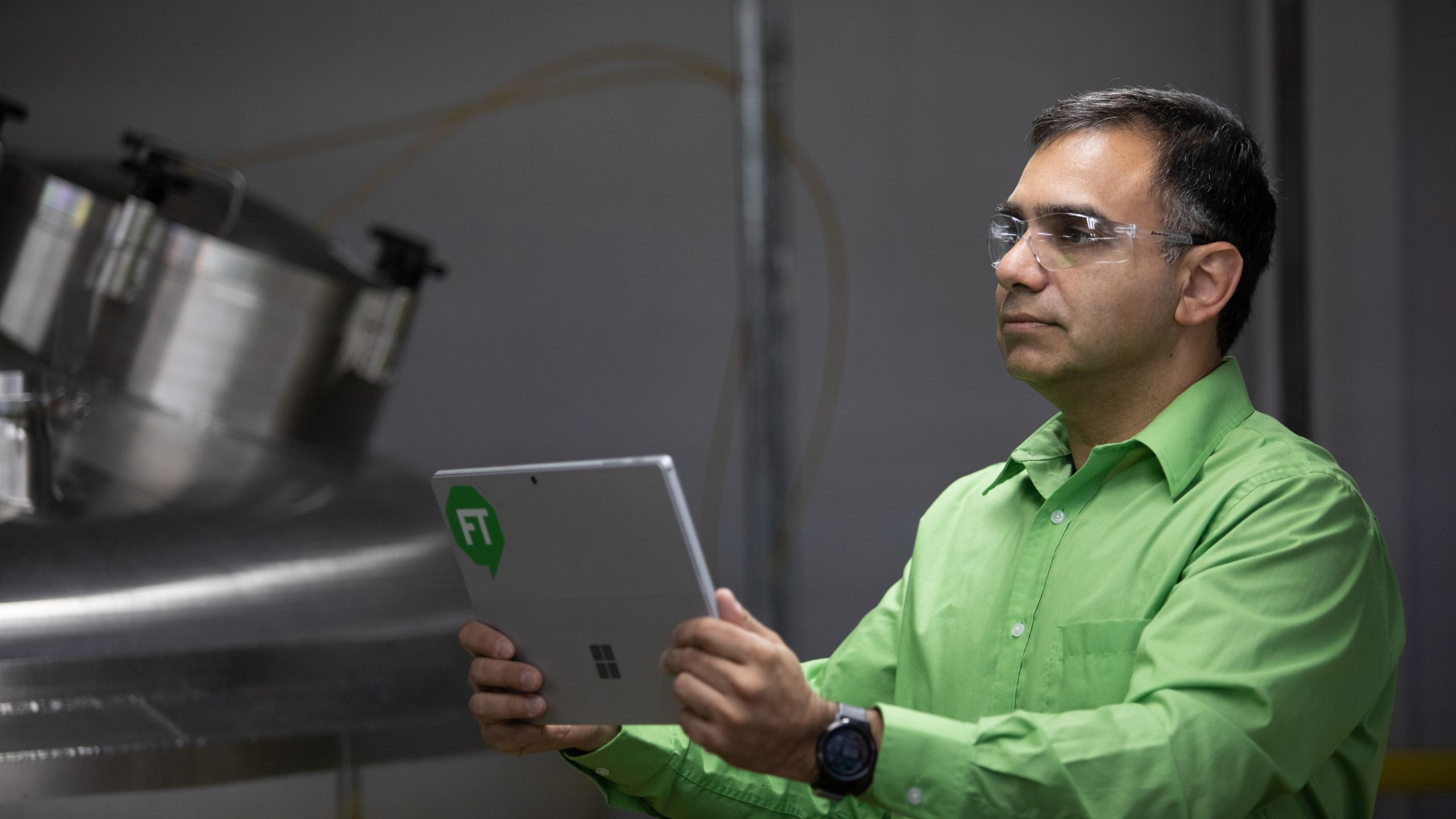Male employee wearing a green shirt and safety glasses holding a tablet with a green FactoryTalk logo assessing process data
