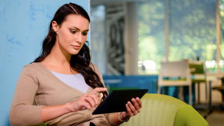 Female employee standing in the lounge area of her company navigating information on her tablet