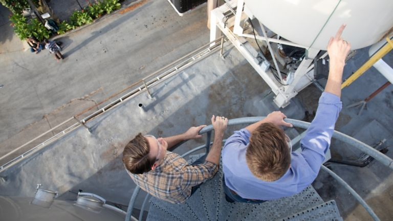 Two engineers standing outside at the top of a winding staircase pointing to a tank holding liquid
