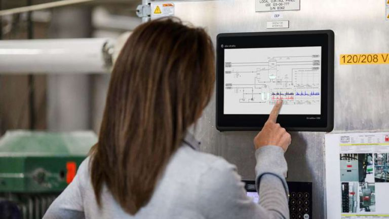 Female employee facing a stand-alone touch monitor retrieving information from FactoryTalk View Machine Edition software