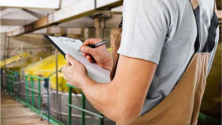 man in factory setting writing on clipboard