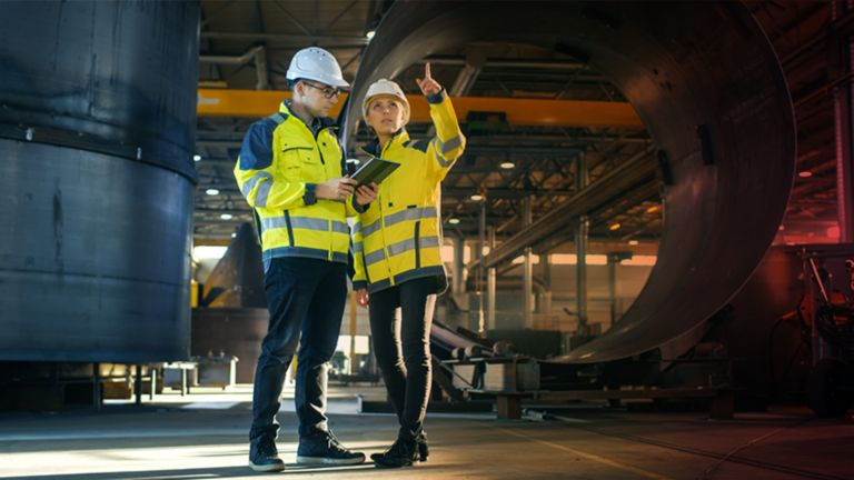 Two employees in a factory wearing safety clothing with one employee pointing to something and the other employee viewing information on a tablet