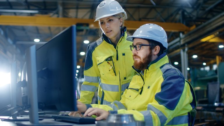 Two employees in the factory viewing a monitor in a factory wearing yellow saftey jackets and white hard hats.