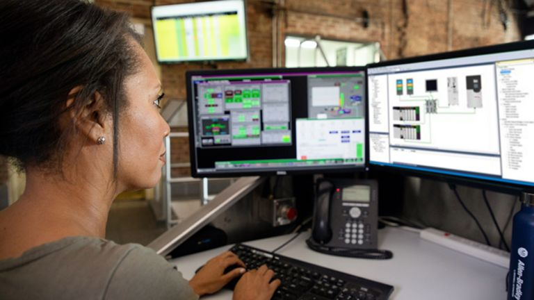 Female employee sitting at her desk viewing multiple monitors typing in information to a software application