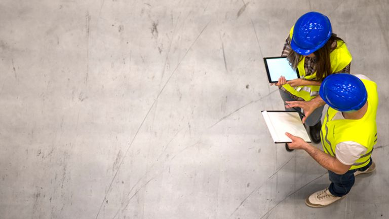 Aerial view of two employees wearing blue hard hats and yellow safety vests viewing information on a tablet