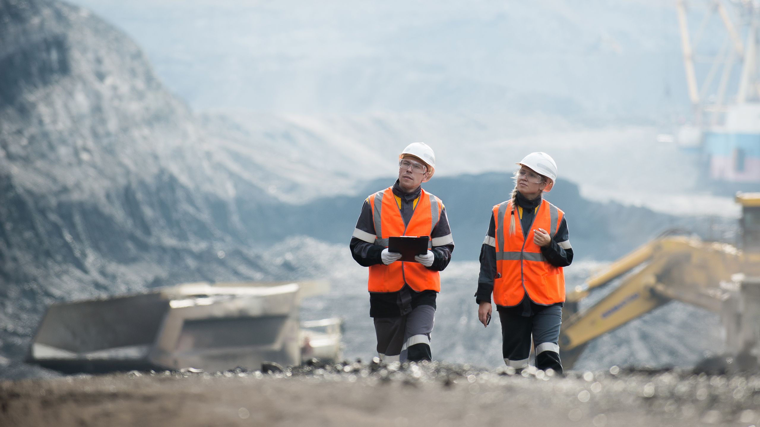 Two mining employees walking through and viewing a mine site