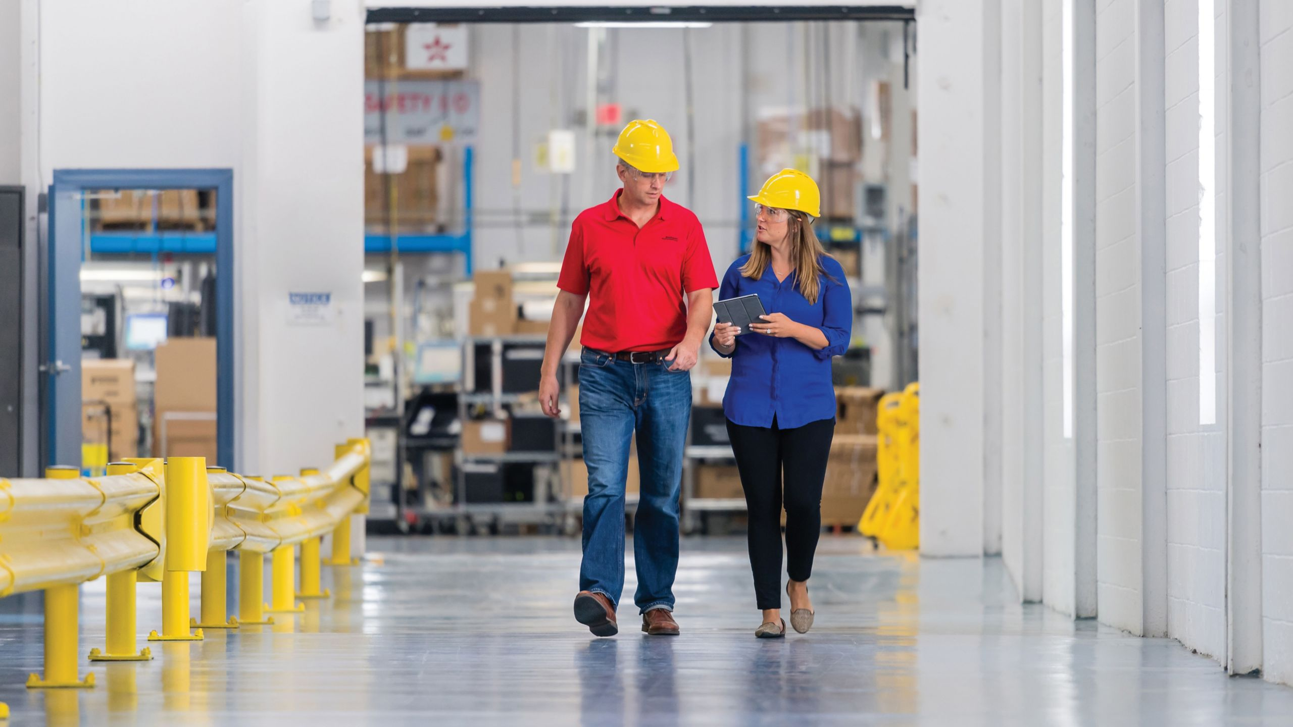 Two employees walking in a plant in deep conversation wearing yellow hard hats