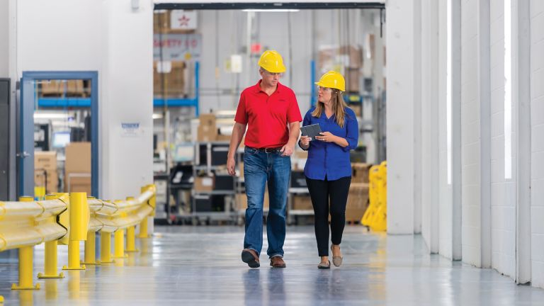 Two employees having a conversion and walking through the plant