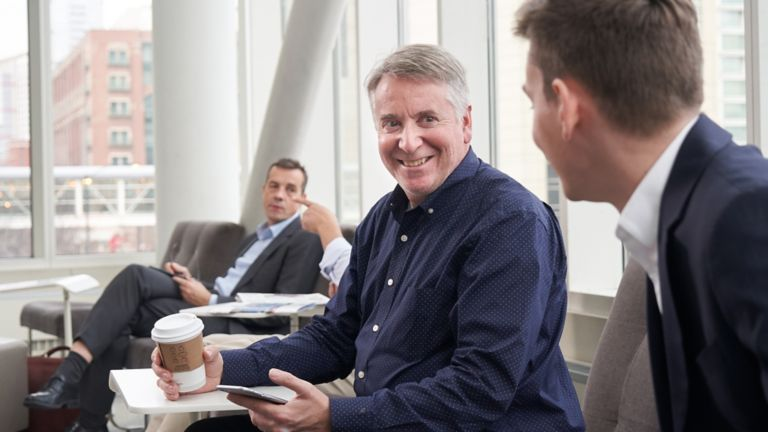 Three executives sitting smiling having a conversation