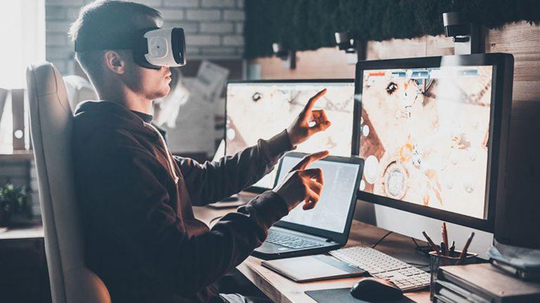 Un empleado sentado en su escritorio frente a dos monitores y su computadora portátil, con un casco de realidad aumentada