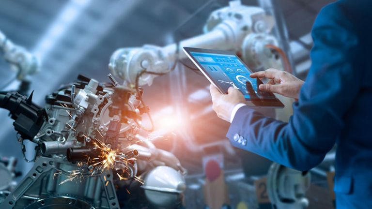 The arms of a man in a blue coveralls holding a tablet in front of a welding robotic arm