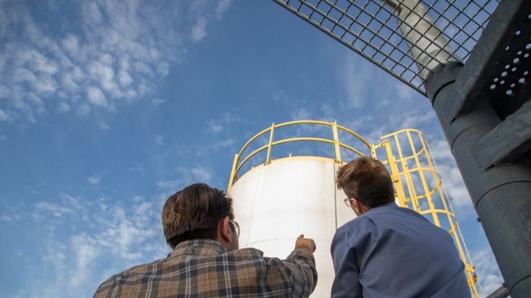two men looking up at a water tank with blue sky and clouds in the background