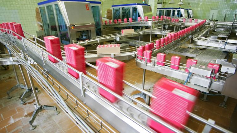 assembly line moving pink containers on a plant floor using smart motor control devices