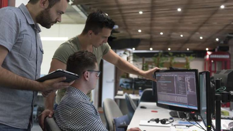 Three engineers reviewing  software on a monitor