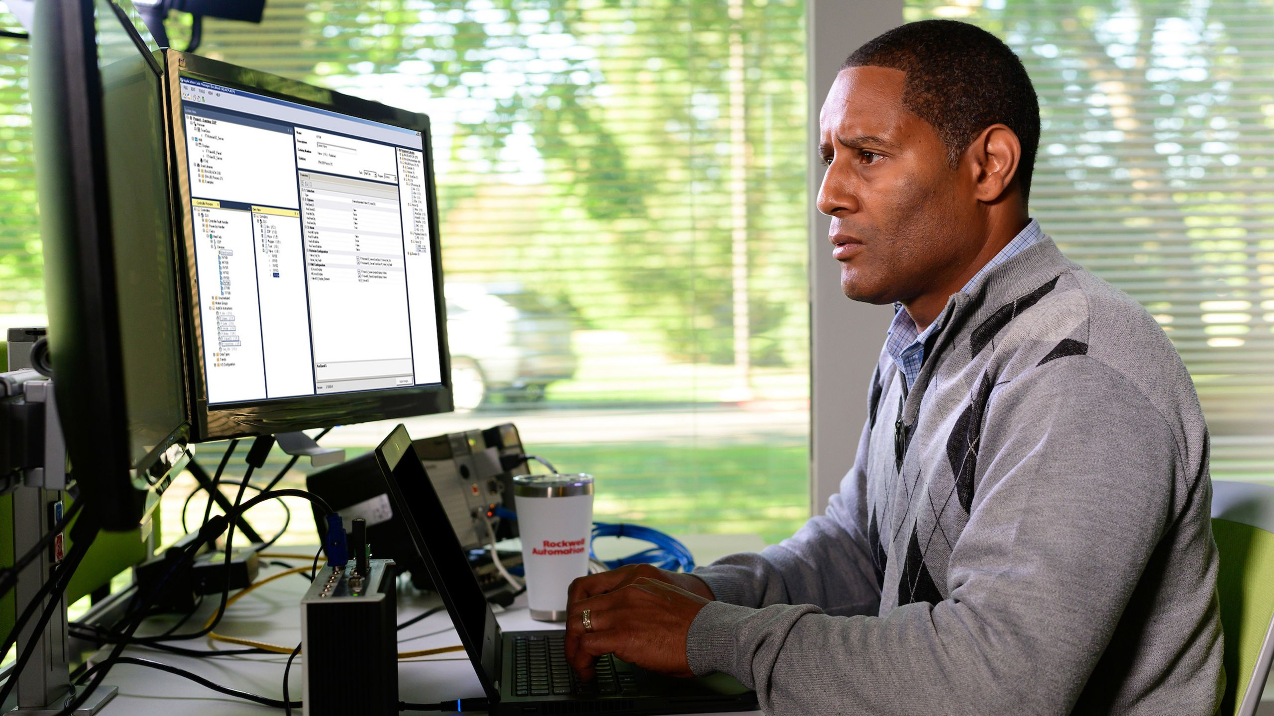 Rockwell Automation employee viewing his monitor and adding information into the Studio 5000 Application Code Manager software