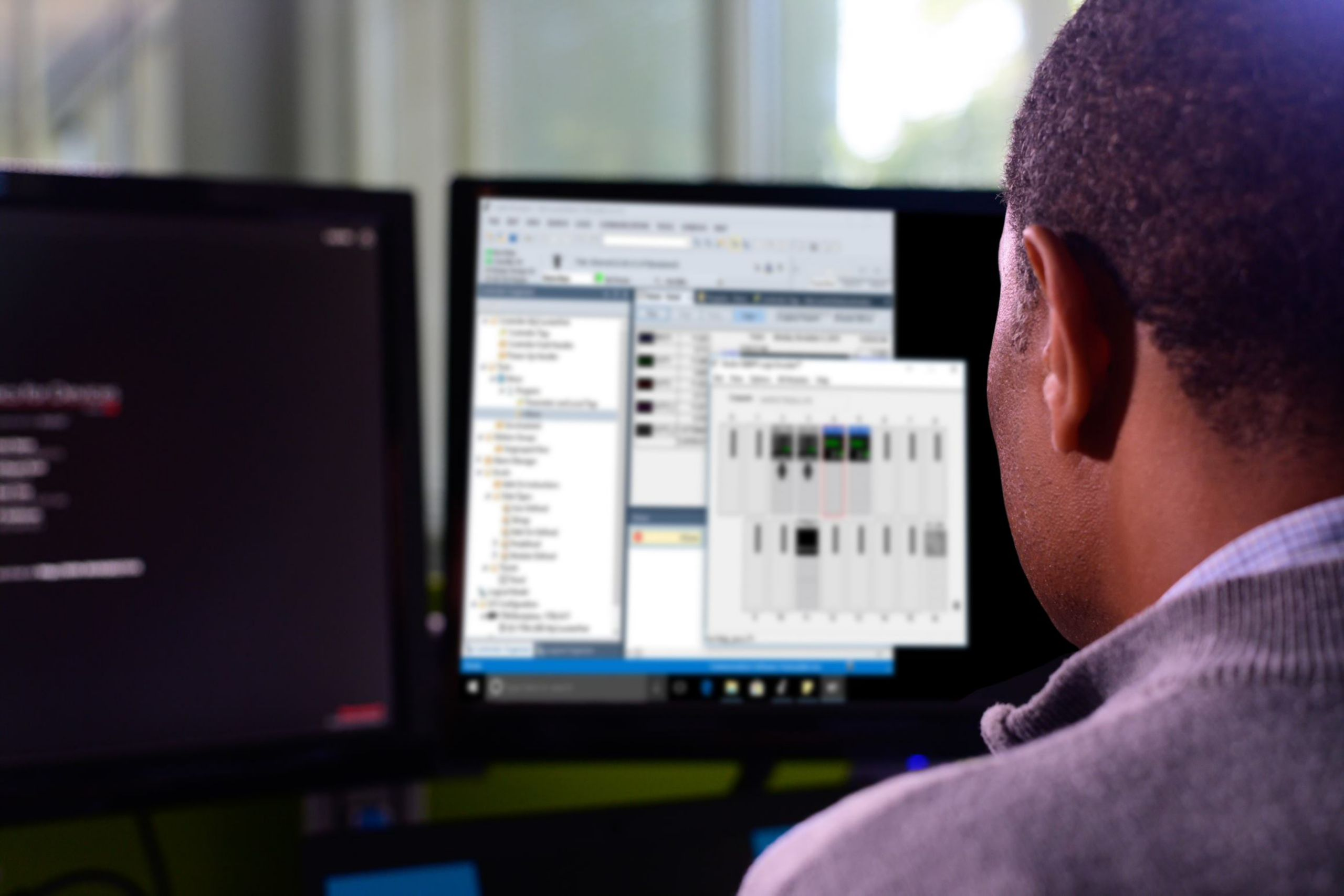 Male employee viewing Studio 5000 Logix Emulate software on his monitors