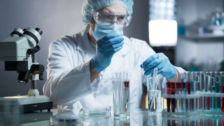 Pharmaceutical lab technician adding drops of liquid into a test tube