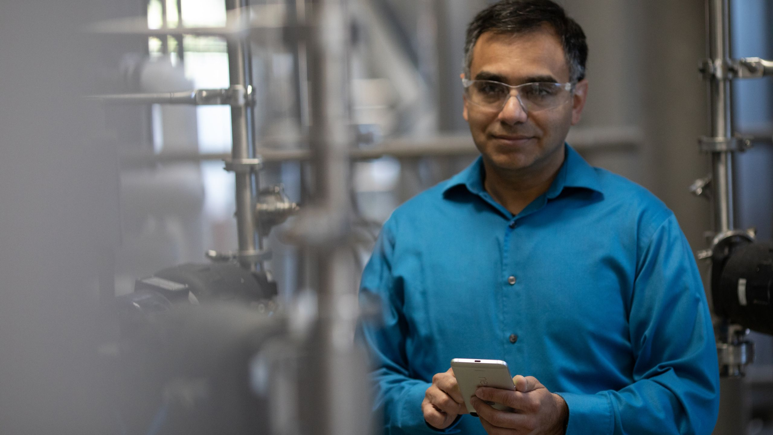 Engineer wearing a blue shirt and safety glasses in a factory looking forward holding his mobile phone