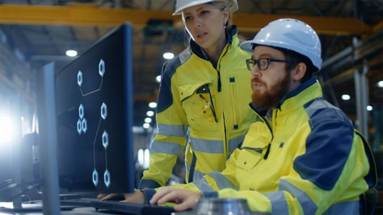 Two factory employees wearing safety clothing viewin information on a monitor
