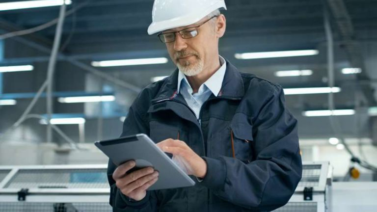 Employee wearing a hard hat in a factory entering information into his tablet