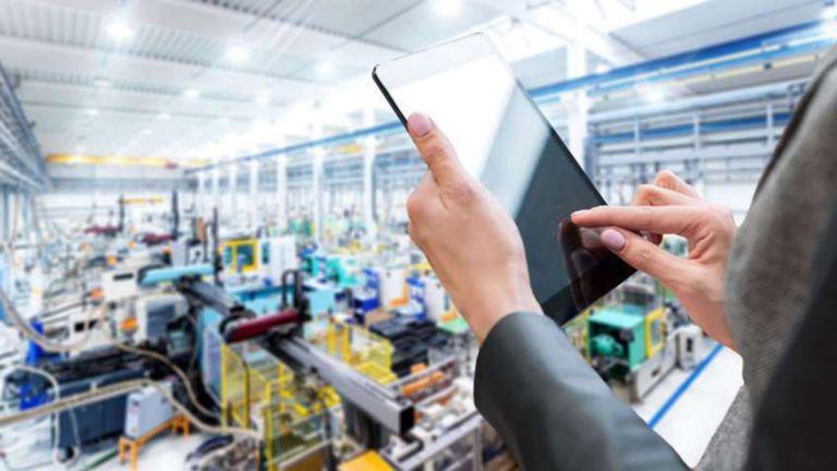 Empleada ingresando datos en una tableta mientras ve una planta de fabricación